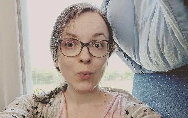 Helene Bockhorst sitzt mit überraschtem Gesichtsausdruck im Zug